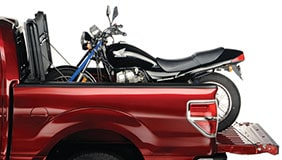 Motorcycle loaded up in a truck bed with a tonneau