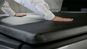 Hand on top of soft folding tonneau cover