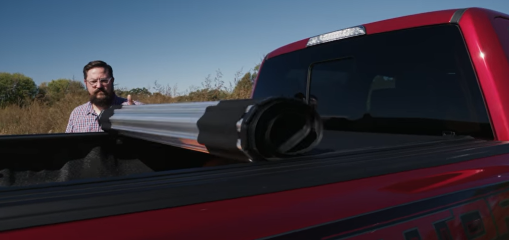 A truck owner rolling down his hard roll-up cover