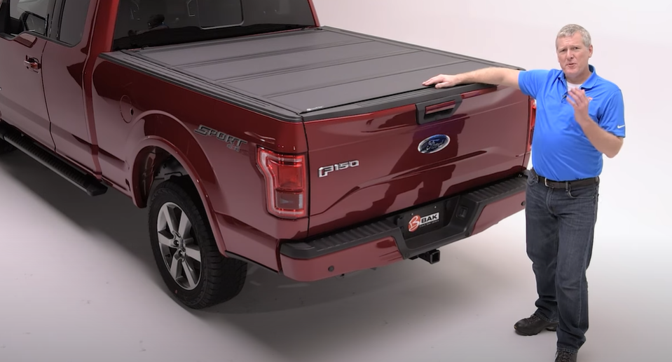 Someone touching a BAKFlip MX4 installed over a truck bed
