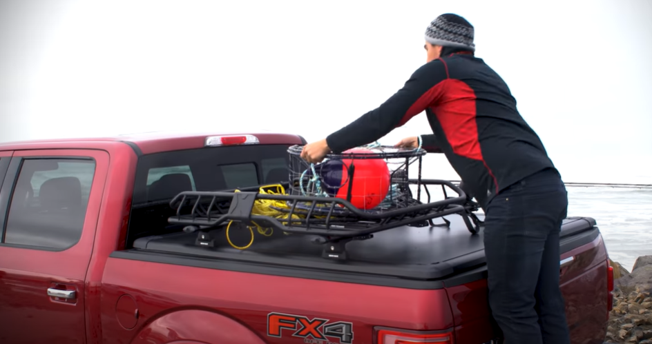 A truck owner loading cargo on a track system installed over a tonneau cover