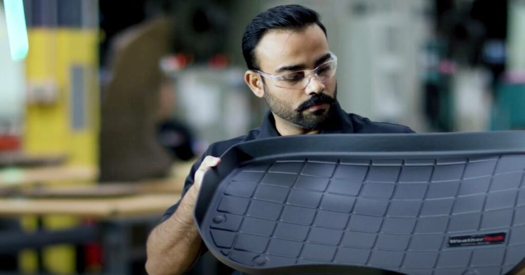 Man holds and inspects one of his clean, heavy-duty, custom all-weather mat from his truck