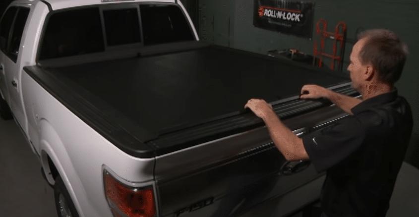 Man operating E-Series Roll-N-Lock tonneau cover