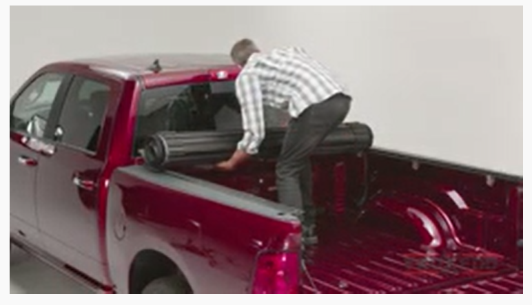 Man installing the cover on the Ram truck bed