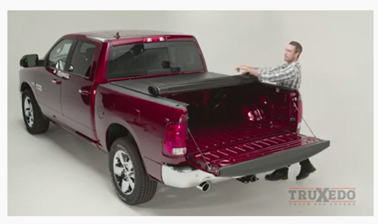 Man unrolling the Ram cover to close it