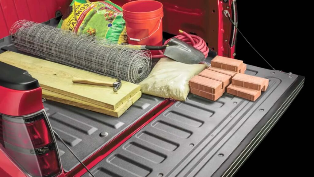 A red Ford F-150 truck bed installed with WeatherTech Techliner Bed Mat and hauling tools